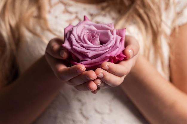 Primer plano de rosa en manos de mujer