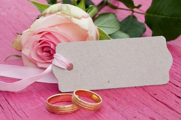 Primer plano de una rosa rosa, una etiqueta con espacio para texto y dos anillos de bodas de oro sobre una mesa rosa
