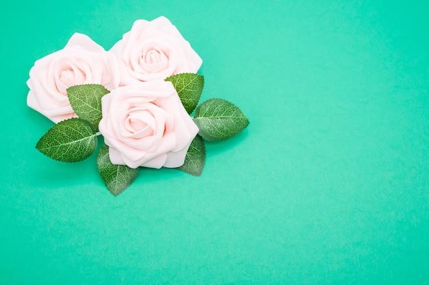 Primer plano de rosas rosadas aislado sobre un fondo verde con espacio de copia