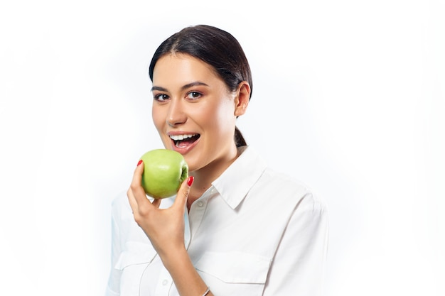 Primer plano del rostro de una mujer comiendo una manzana verde.
