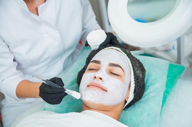 Primer plano de rostro de mujer en procedimiento de máscara de arcilla blanca en salón de belleza. mascarilla exfoliante facial, tratamiento de belleza spa, concepto de cuidado de la piel.