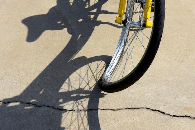 Primer plano de una rueda de bicicleta torcida, proyectando sombras surrealistas en la acera