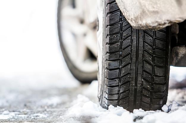 Primer plano de la rueda del coche en neumático de invierno en carretera nevada
