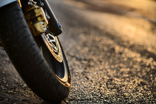 Primer plano de la rueda delantera de una motocicleta en los rayos del sol.