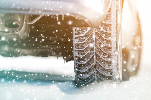 Primer plano de las ruedas del coche neumáticos de goma en la nieve profunda del invierno