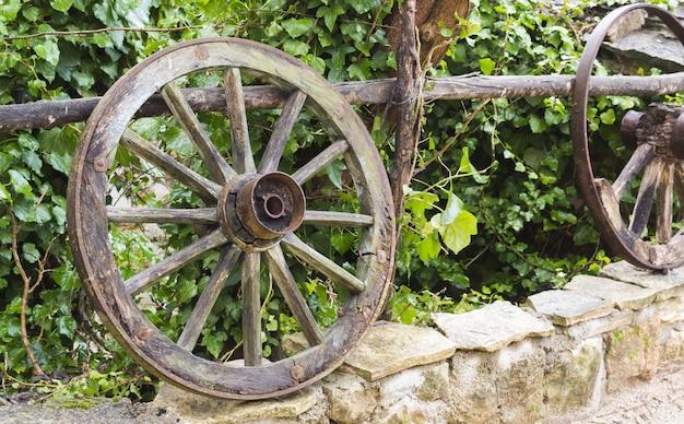 Primer plano de ruedas de madera en un borde de piedra delante de las plantas verdes
