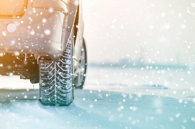 Primer plano de las ruedas de los neumáticos de goma en la nieve profunda del invierno. concepto de transporte y seguridad.