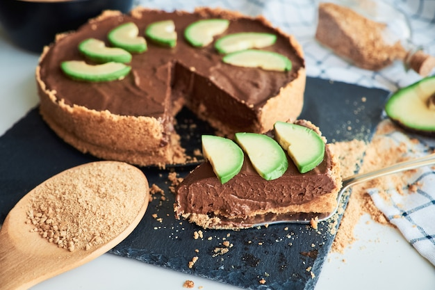 Primer plano de sabroso pastel de chocolate vegano crudo hecho de aguacate y plátano. comida vegetariana saludable.