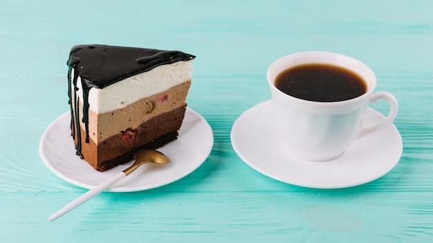 Primer plano de un sabroso pastel cremoso con una cuchara y una taza de té