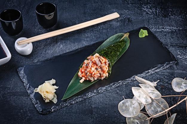 Primer plano de sabroso sushi roll de mano con anguila y caviar tobico servido en plato de piedra oscura con salsa de soja y jengibre. copia espacio temaki, cocina japonesa. comida sana