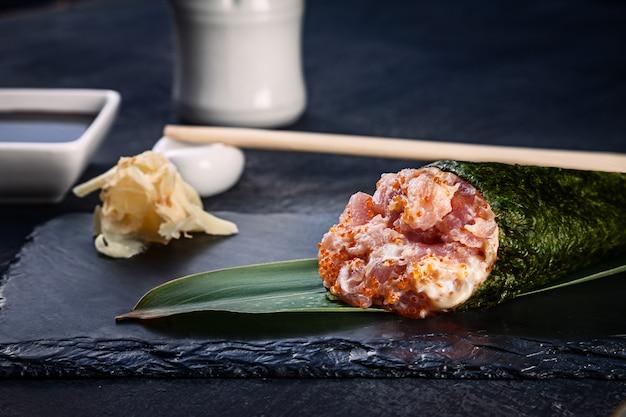 Primer plano de sabroso sushi roll de mano con atún y caviar tobico servido en plato de piedra oscura con salsa de soja y jengibre