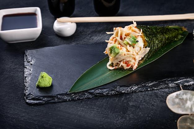 Primer plano de sabroso sushi roll de mano con cangrejo y caviar tobico servido en plato de piedra oscura con salsa de soja y jengibre