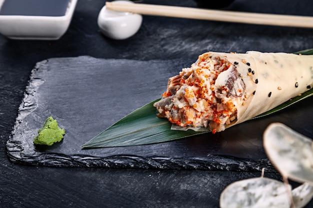 Primer plano de sabroso sushi roll a mano en mamenori con anguila y caviar tobico servido en plato de piedra oscura con salsa de soja y jengibre