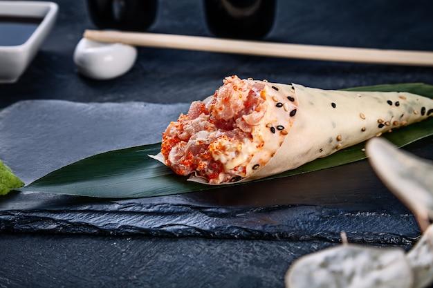 Primer plano de sabroso sushi roll a mano en mamenori con atún y caviar tobico servido en plato de piedra oscura con salsa de soja y jengibre