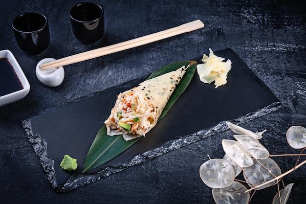 Primer plano de sabroso sushi roll de mano en mamenori con cangrejo y caviar tobico servido en plato de piedra oscura con salsa de soja y jengibre. copia espacio temaki, cocina japonesa. comida sana