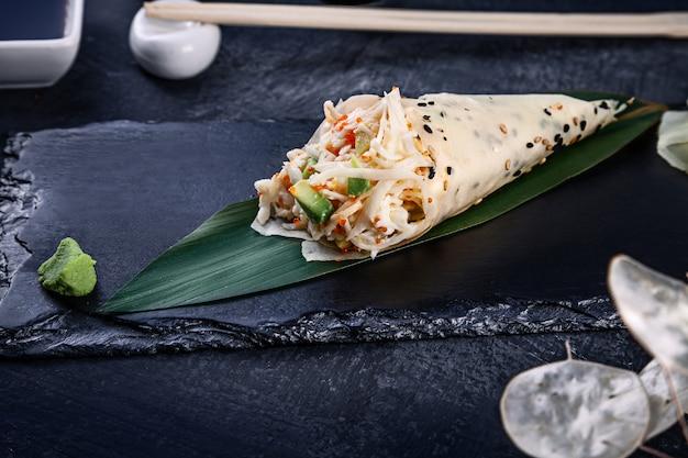 Primer plano de sabroso sushi roll a mano en mamenori con cangrejo y caviar tobico servido en plato de piedra oscura con salsa de soja y jengibre