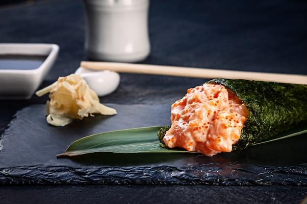 Primer plano de sabroso sushi roll de mano con salmón y caviar tobico servido en plato de piedra oscura con salsa de soja y jengibre