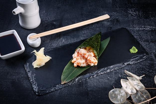 Primer plano de sabroso sushi roll de mano con vieira y caviar tobico servido en plato de piedra oscura con salsa de soja y jengibre. copia espacio temaki, cocina japonesa. comida sana