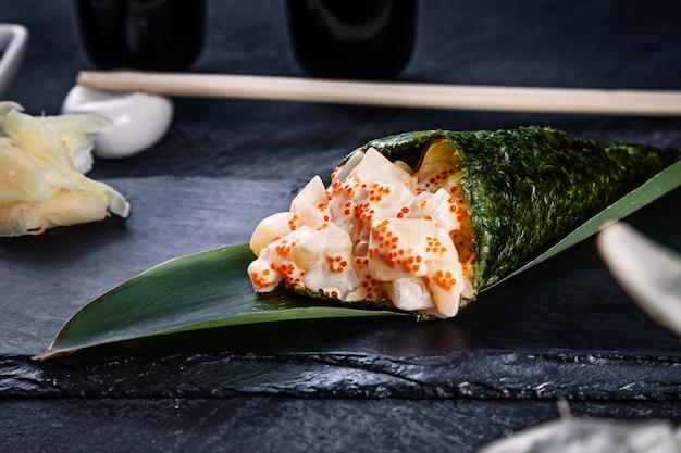Primer plano de sabroso sushi roll de mano con vieira y caviar tobico servido en plato de piedra oscura con salsa de soja y jengibre