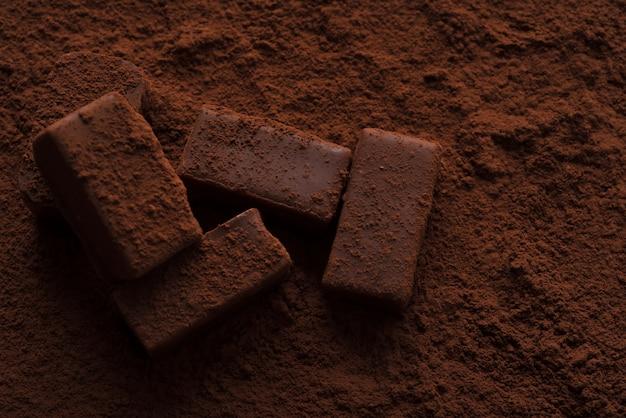 Primer plano de sabrosos dulces de chocolate oscuros cubiertos de chocolate en polvo
