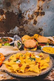 Primer plano de sabrosos nachos mexicanos; hamburguesa; maíz; tomates y tacos de carne mexicana