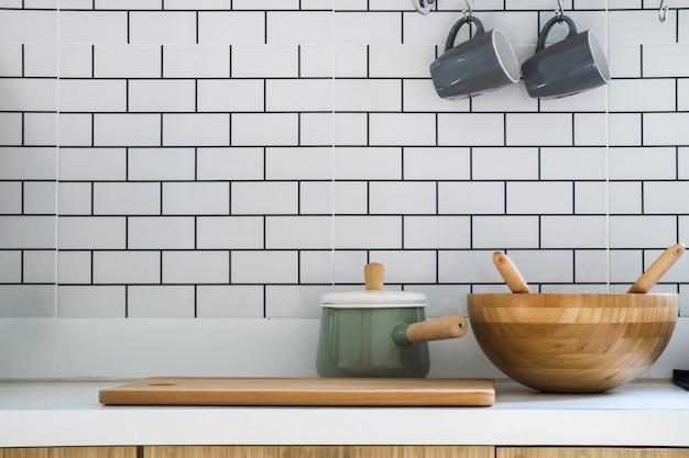 Primer plano de la sala de cocina con olla, cortar leña, tina de madera y dos tazas de café de cerámica puesta en mostrador moderno