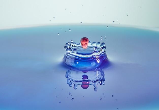 Primer plano de salpicaduras de agua, colisión de gotas de colores y creación de coronas, arte conceptual con efecto abstracto.