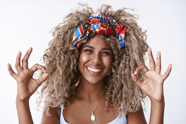 Primer plano satisfecho y feliz, chica rubia de pelo rizado con peinado afro, nariz perforada, elegante diadema, sonriendo con aprobación, muestra bien, gesto de acuerdo satisfecho con un buen servicio, de pie encantado