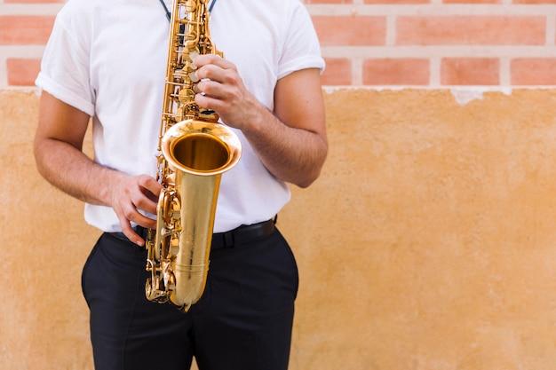 Primer plano de saxofón tocado por el hombre.