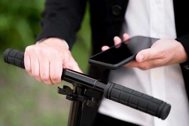 Primer plano scooter de desbloqueo masculino con teléfono móvil