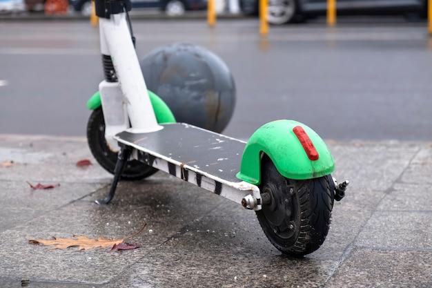 Primer plano de un scooter eléctrico estacionado cerca de la carretera con coches en movimiento, clima húmedo y nublado en bucarest, rumania