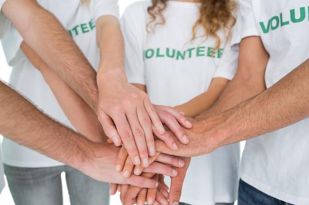 Primer plano sección media de voluntarios con las manos juntas