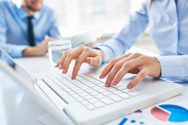 Primer plano de secretaria escribiendo en el portátil