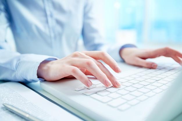 Primer plano de secretaria escribiendo en el teclado