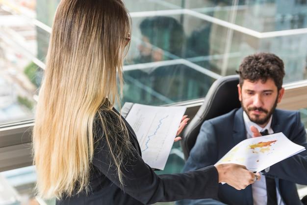 Primer plano de la secretaria de sexo femenino que da el mapa al encargado de sexo masculino en el lugar de trabajo