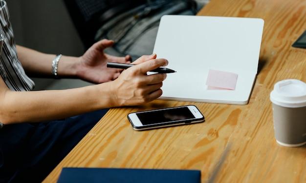 Primer plano de la secretaria tomando notas en una reunión
