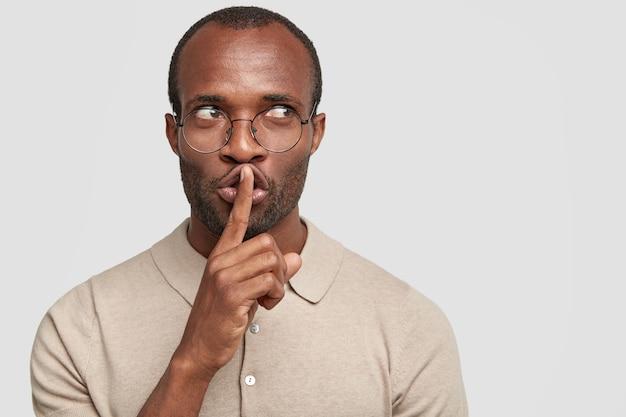 Primer plano de secreto macho afroamericano hace gesto de silencio