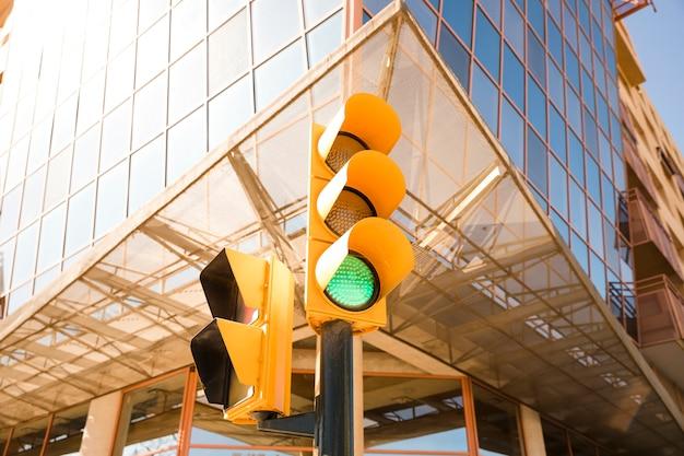 Primer plano de semáforo verde cerca del moderno edificio corporativo