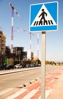 Primer plano de la señal de advertencia de peatones en una calle urbana con sitio de construcción