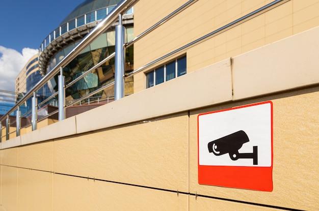 Primer plano de señal de advertencia sobre el área de observación de video en la pared del edificio de color beige