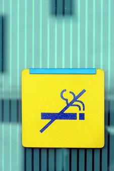 Primer plano de la señal amarilla de no fumar en la pared de vidrio verde