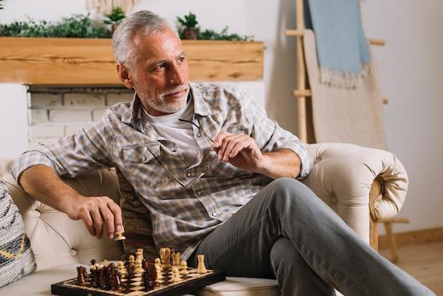 Primer plano de senior hombre sentado en el sofá jugando al ajedrez