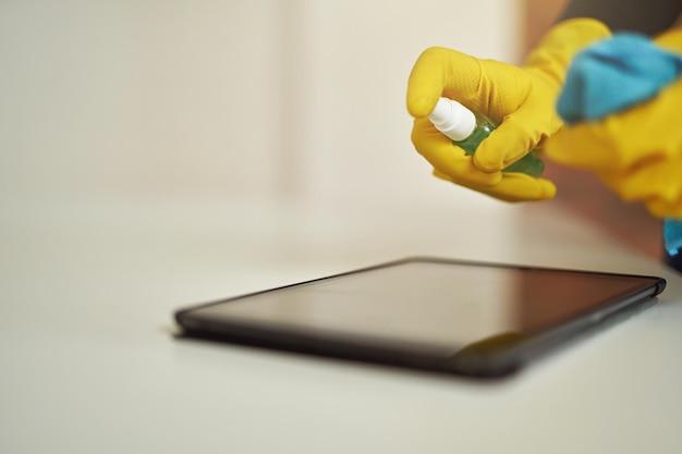 Primer plano de la señora de la limpieza en guantes de goma con aerosol desinfectante antibacteriano y paño mientras