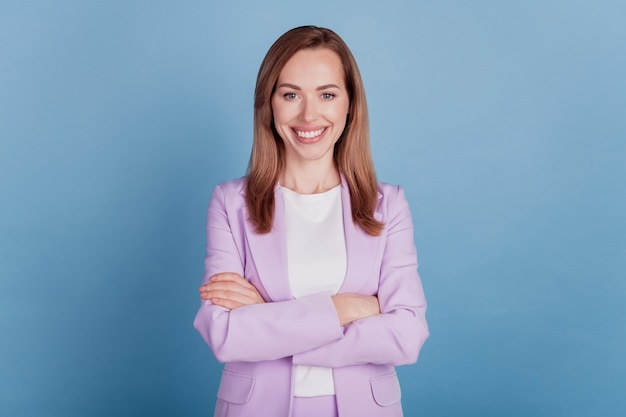 Primer plano de una señora de negocios mandona con dientes sonrisa mirada cámara brazos cruzados sobre pared azul