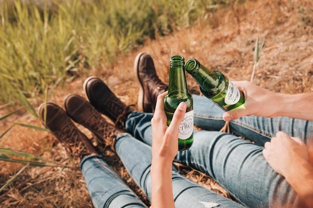 Primer plano sentado pareja bebiendo cerveza