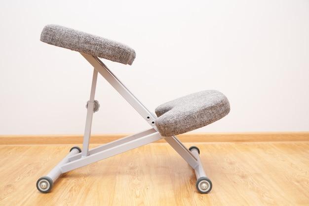 Primer plano de la silla de rodillas ergonómica ortopédica en el fondo de la pared del hogar, cuidado de la salud de la espalda