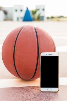 Primer plano de smartphone y baloncesto