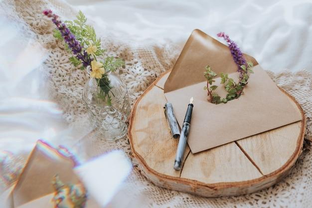Primer plano de un sobre con flores y un bolígrafo