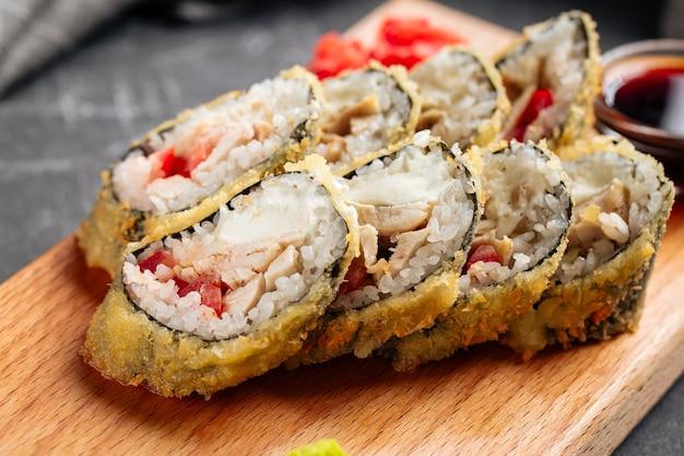 Primer plano sobre rollos de sushi tempura asado con pollo y tomate