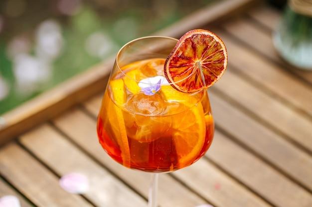 Primer plano sobre un vaso de cóctel aperole spritz aderezado con una rodaja de naranja